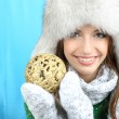 Beautiful smiling girl with Christmas ball on blue background — Stock Photo