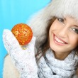 Stock Photo: Beautiful smiling girl with Christmas ball on blue background
