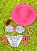 Swimsuit and beach items on green background — Stock Photo