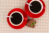Red cups of strong coffee with chocolate bars on squared background — Stock Photo