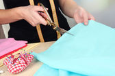 Cutting fabric with tailors scissors — Stock Photo