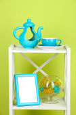 Composition of various home furnishing on white shelf on green wall background — Stockfoto