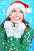 Beautiful smiling girl in New Year hat on blue background — Stock Photo