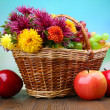 Composition with beautiful flowers in wicker basket and fruits, on bright background — Stock Photo #36601843
