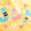 Word Joy created with brightly colored knitting yard on fabric background — Stock Photo