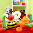 Simple balloon animals and other toys on shelves, on bright background — Stock Photo