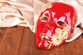 Mask on golden fabric on wooden background — Stock Photo