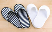 Striped and white slippers on wooden background — Stock Photo