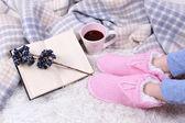 与温暖的格子,书,杯喝些热饮料和女性的腿,对彩色地毯背景组成 — 图库照片