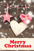 Decorative hearts and star on rope, on wooden background — Stock Photo