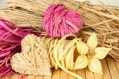 Decoratieve stro voor met de hand gemaakt, bloem en harten van stro, op houten achtergrond — Stockfoto