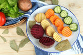 Beautiful sliced vegetables, on plate, on wooden background — Stockfoto
