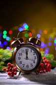 Christmas decorations and retro alarm clock on wooden table, on bright background — Foto Stock