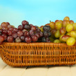 Fresh grape on wicker mat on bright background — Stock Photo #36685775