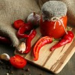 Composition with salsa sauce in glass jar,, red hot chili peppers and garlic, on sackcloth, on wooden background — Stock Photo #36685831
