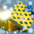 Gift box with bright light on it on blue background — Стоковая фотография