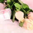Beautiful roses and gift on pink cloth, close up — Stock Photo