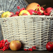 Juicy apples and pumpkin in wooden basket on table close-up — Foto Stock