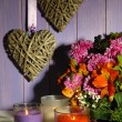 Flowers composition in crate with candles on table on wooden background — Stock Photo