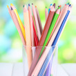 Colorful pencils in glass on wooden table on natural background — Stock Photo