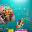 School supplies in supermarket carts on blackboard background — Stock Photo #36687197