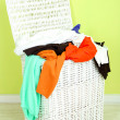 Full laundry basket  on wooden floor on green wall background — Stock Photo