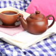 Stock Photo: Cup and teapot on wooden tray on fabric background