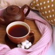 Cup and teapot with scarf on bed close up — Stock Photo