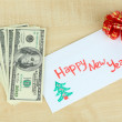 Dollar bills in envelope as gift at New year on wooden table close-up — Stock Photo #36687657