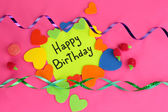 """Card """"Happy Birthday"""" surrounded by festive elements on pink background — Stock Photo"""