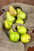 Pears on cutting board, on sackcloth background — Stock Photo