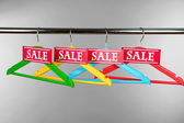 Wooden clothes hangers as sale symbol on gray background — Stockfoto