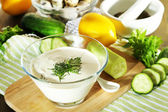 Cucumber yogurt in glass bowl, on color napkin, on wooden background — Stock Photo