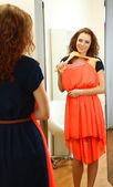 Beautiful girl trying dress near mirror in room — 图库照片