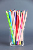 Colorful pencils in glass on gray background — Stock Photo
