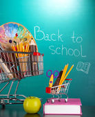 School supplies in supermarket carts on blackboard background — Stock Photo