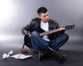 Junge musiker gitarre zu spielen, auf grauem hintergrund — Stockfoto