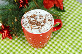 Hot chocolate with cream in color mug, on napkin, on Christmas decorations background — 图库照片