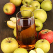 Useful apple juice with apples around on wooden table — Photo
