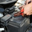 Car mechanic uses battery jumper cables to charge dead battery — Stok fotoğraf