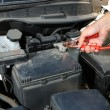 Car mechanic uses battery jumper cables to charge dead battery — Stockfoto
