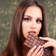 Portrait of beautiful young girl with chocolate on shiny background — Stock Photo