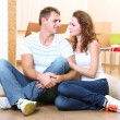 Young couple with boxes in new home on room background — Foto Stock