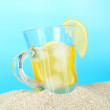 Cold tea in sand on blue background — Stock Photo