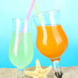 Beach cocktails in sand on blue background — Stock Photo
