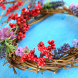 Wreath of dry branches with flowers and viburnum on wooden table close-up — Stock Photo