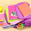 Purple backpack with school supplies on wooden background — Stock Photo #36698163