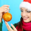 Beautiful smiling girl with Christmas ball on blue background — Stock Photo #36698551