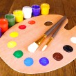 Wooden art palette with paint and brushes on table close-up — Stock Photo