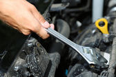 Hand with wrench. Auto mechanic in car repair — Stock Photo